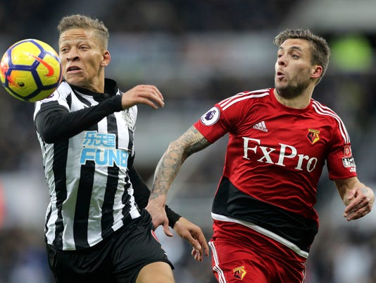 Newcastle United's Dwight Gayle, left, and Watford's Kiko Femenia battle for the ball during their English Premier League soccer match at St James' Park in Newcastle, England, Saturday Nov. 25, 2017. (Owen Humphreys/PA via AP)
