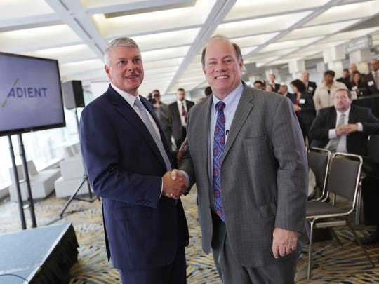 Adient Chairman and CEO Bruce McDonald, left and Detroit mayor Mike Duggan shake hands after announcing plans to bring Adient's headquarters to the Marquette Building downtown Detroit during a press conference at Cobo Center in Detroit on Wednesday, Nov. 30, 2016.