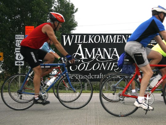Bicyclists pass by a sign welcoming them to the Amana