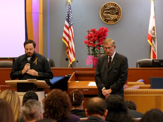 Holy Trinity Catholic Church Rev. Joshua Clifton delivers an invocation alongside Monterey County District Attorney Dean D. Flippo.