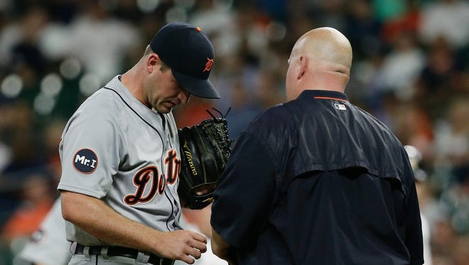 Jordan Zimmermann of the Detroit Tigers looks at his fingernail with the trainer in the first inning.