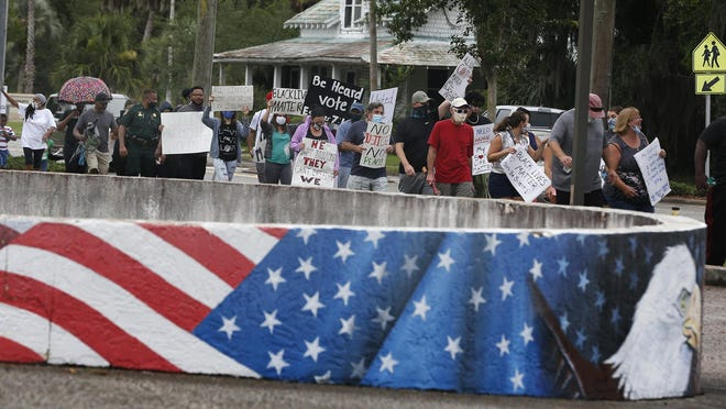 Protestors stage a peaceful march through the city streets of Bunnell, Saturday, June 6, 2020.
