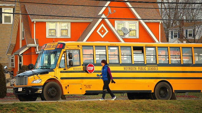 A Weymouth school bus drives along Commercial Street.