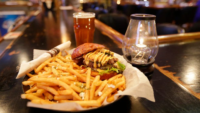 A glass of ale is nestled alongside a craft burger called A Bit of Heat, topped with Caribbean jack cheese, a house-made jalapeno popper and sriracha aioli, at Brickhouse Craft Burgers & Brews in De Pere.
