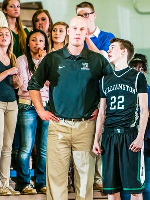 Williamston boys basketball head coach Jason Bauer is shown in 2014 with player Riley Lewis (22). Bauer is undergoing treatment for brain tumors and his team will be coached Friday in a district championship game by assistant Tom Lewis, Riley's father.