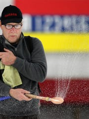 John Worotny of Wausau uses a special sprinkling device Sunday to add droplets of water that freeze and blend in with the pebbled curling surface for the Badger State Winter Games at the Wausau Curling Center.