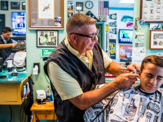 Bob Johns gives his grandson Jacob, 13, a haircut at the Naples Park Barber Shop on Thursday, June 14, 2018. Johns, owner, gave his first haircut when he was 13 years old.