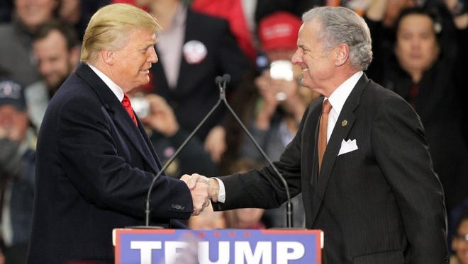 Then-Republican presidential candidate Donald Trump speaks with South Carolina Lt. Gov. Henry McMaster after McMaster introduced him to a large crowd at the T. Ed Garrison Livestock Arena on Wednesday.