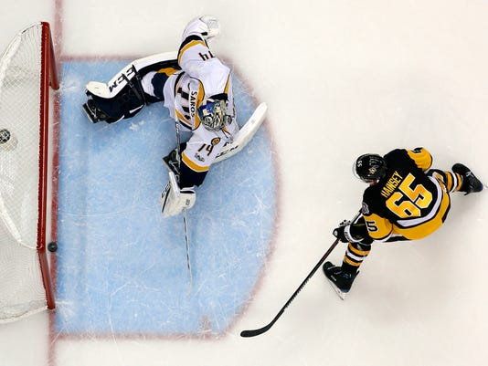 Pittsburgh Penguins' Ron Hainsey (65) gets a shot behind Nashville Predators goalie Juuse Saros (74) during the second period of Game 5 of the NHL Stanley Cup Final, Thursday, June 8, 2017, in Pittsburgh. The Penguins won 6-0. (AP Photo/Gene J. Puskar)