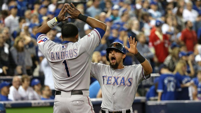Rougned Odor celebrates scoring the go-ahead run in the 14th inning with Elvis Andrus.