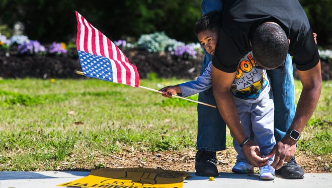 """Legin Payne, 3, waves an American flag as his father, Nigel Payne, a Memphis police officer, ties his shoe during a union protest at the intersection of Poplar and Highland on Saturday, to delay a vote on an ordinance changing the way Memphis City Council resolves labor negotiation stalemates. 13 unions are working on a compromise with Mayor Jim Strickland's administration and the council that would change the """"impasse ordinance"""" without removing necessary protections for employees. A vote on the ordinance will be held during a City Council meeting on Tuesday at 3:30 p.m."""