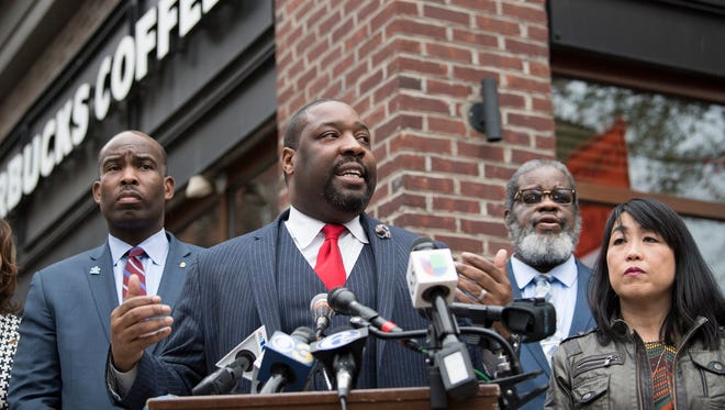 Philadelphia City Councilman, Kenyatta Johnson, center, flanked by two fellow members, speaks at the podium during a press conference outside the Starbucks on 18th & Spruce Streets in Philadelphia on April 16, 2018. Two black men were arrested last week in a video incident that went viral over the weekend.