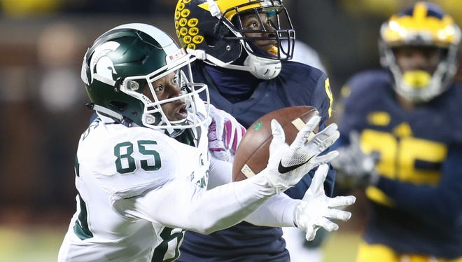 Michigan State's Macggarrett Kings Jr is defended by Michigan's Channing Stribling during the third quarter of MSU's 27-23 win Saturday in Ann Arbor.
