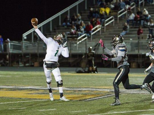 Under pressure from Desert Hills defenders, Snow Canyon quarterback Matt Kitchen throws the ball downfield Friday, Nov. 6, 2015.