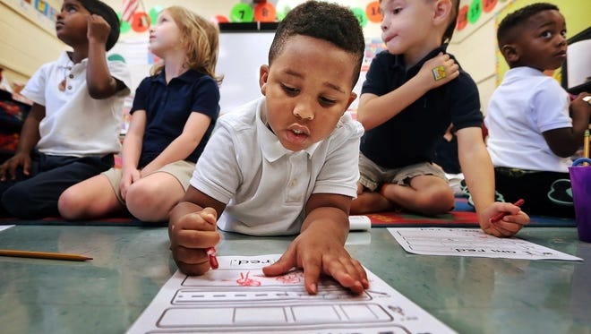 Grahamwood Elementary kindergarten student Christopher Beaumont (center) works on a colors assignment in Myra Jenkins' class. Grahamwood is planning a 10-classroom and gymnasium addition next school year, part of the district's efforts to increase high-quality options.