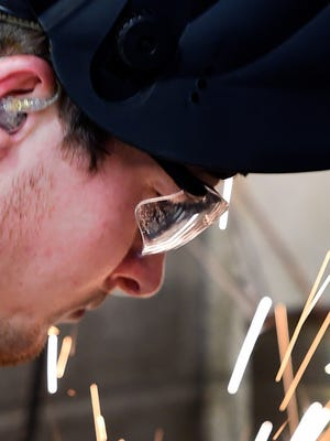 MIKE LAWRENCE / THE GLEANER  Henderson Community College welding student Kenny Yoder uses a grinder to clean the edges of the steel plate he is using to practice a tig welding technique on, April 14, 2015.