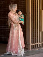 Maliha Avais, 18, holds her cousin Imaan Malik, 1,