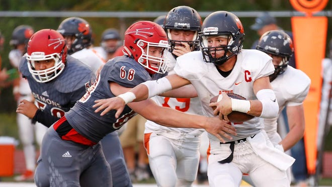 Durango's Adam Short, left, grabs Aztec quarterback Cody Smith in Friday's game at Durango High School. The Demons won, 35-14.