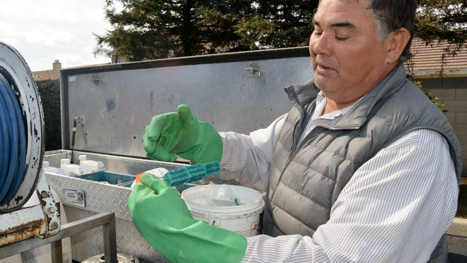 Armando Gallegos, a Bayne Pest Control applicator hold the poison that is placed in a box trap which attracts rats, Feb. 28, 2018.