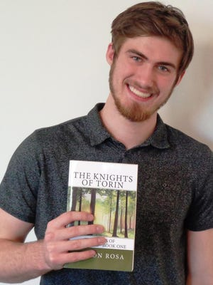 """Teen author Colson Rosa displays the book he published at age 12, """"The Knights of Torin"""" which launched the five-book series of """"The Tales of Amcronos."""""""