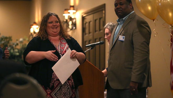 Derrick Jackson, director of communications at San Angelo ISD, hands out grants from the San Angelo Schools Foundation to district teachers during a small ceremony at the LeGrand Alumni and Visitors Center on Monday, Nov. 13, 2017.