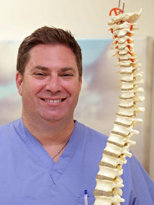 Dr. Daniel Lieberman, MD, in his new new Phoenix Spine Surgery Center, with a model of the spinal column as seen in Goodyear on June 2, 2015.