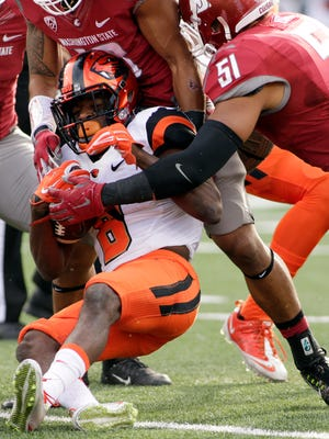 Washington State linebacker Frankie Luvu (51) and safety Shalom Luani, back, bring down Oregon State wide receiver Victor Bolden (6) during the second half of an NCAA college football game, Saturday, Oct. 17, 2015, in Pullman, Wash. Washington State won 52-31.