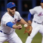 New York Mets third baseman Eric Campbell bobbles a ground ball hit by Atlanta Braves' Nick Markakis during the third inning of a baseball game, Tuesday, April 21, 2015, in New York. Markakis reached first base safely and Campbell was charged with an error.