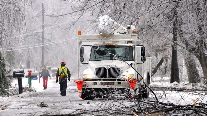 Utility workers in a north Lansing neighborhood on Sunday, Dec. 22, 2013.
