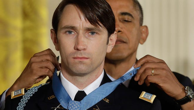 President Barack Obama awards the Medal of Honor to former Army Capt. William D. Swenson of Seattle during a ceremony in the East Room at the White House in Washington on Oct. 15, 2013. Swenson was being awarded the Medal of Honor for his actions in a lengthy battle against Taliban insurgents in the Ganjgal valley near the Pakistan border on Sept. 8, 2009, which claimed the lives of five Americans, 10 Afghan army troops and an interpreter.