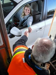 Jessica Smith of Anderson pays Lee Currens, toll collector, at the Southern Connector toll plaza in Greenville.