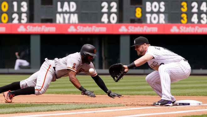 San Francisco Giants center fielder Denard Span (2) slides back to first against Colorado Rockies first baseman Mark Reynolds (12) at Coors Field in 2016. The Rockies need better defense in 2017 if they want to contend for a playoff spot.