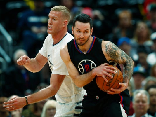 Los Angeles Clippers guard J.J. Redick, front, pulls in a loose ball in front of Denver Nuggets center Mason Plumlee in the first half of an NBA basketball game Thursday, March 16, 2017, in Denver. (AP Photo/David Zalubowski)