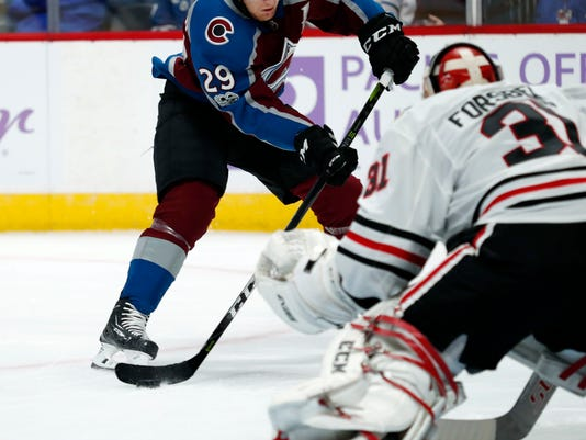 Colorado Avalanche center Nathan MacKinnon, back, fires the puck at Chicago Blackhawks goalie Anton Forsberg, of Sweden, in the first period of an NHL hockey game Saturday, Oct. 28, 2017, in Denver. (AP Photo/David Zalubowski)