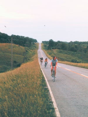 John Karras and Donald Kaul bike from Des Moines to Iowa City in 1971 — two years before they founded the Register's Annual Great Bicycle Ride Across Iowa (RAGBRAI). Here, Ann Karras (John's wife) leads a line of bicyclists just outside of Iowa City.
