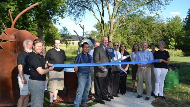 """Iowa City artist Bouunak Thammavong, along with members of the Urbandale Public Art Committee, cut a ceremonial ribbon in 2012 to celebrate the installation of """"Across Currents,"""" a new sculpture in Walker Johnston Park. The sculpture features two steel fish -- one stainless, one rusty Corten -- which represent different backgrounds."""