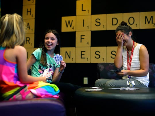 From left, Annabella Robinett, 7, Avery Radke, 7, and Kayla Petrosky, recreational aide and lead summer camp counselor, play a game of go-fish in the game room during the after-school program at the Salvation Army's Ray & Joan Kroc Corps Community Center in Green Bay on Monday, June 6, 2016.