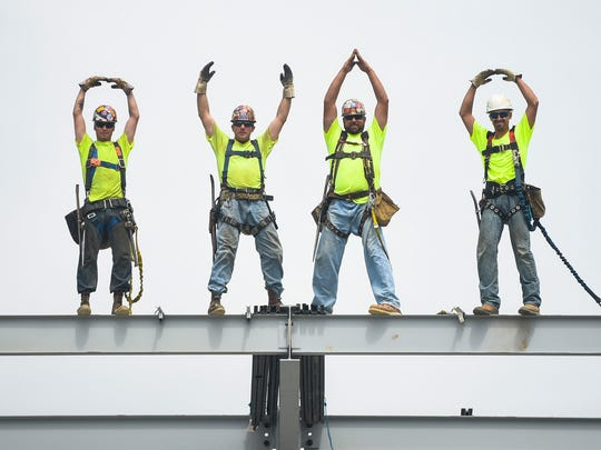 Workers form the familiar O-H-I-O after placing a beam