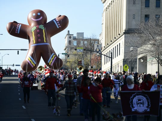 A ginger bread man balloon is guided down Broadway during the Nashville Christmas Parade on Saturday, Dec. 5, 2015, in Nashville, Tenn.