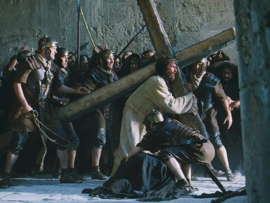 Jim Caviezel, portraying Jesus Christ, carries a cross in 'The Passion of the Christ.' The actor says he and director Mel Gibson are working on a follow-up film.