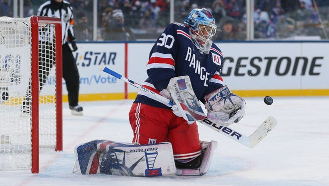 New York Rangers goaltender Henrik Lundqvist makes a save against the Buffalo Sabres during overtime in the 2018 Winter Classic hockey game at Citi Field.