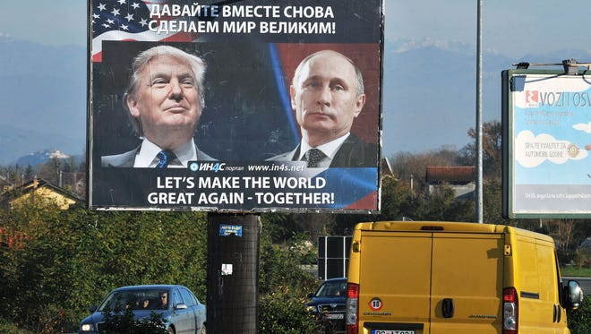 Cars pass by a billboard showing US President-elect Donald Trump and Russian President Vladimir Putin placed by pro-Serbian movement in the town of Danilovgrad on November 16.   Russian President Vladimir Putin and Donald Trump spoke on the phone on November 15, evening and agreed on the need to normalise ties between Washington and Moscow, the Kremlin said.       / AFP / Savo PRELEVIC        (Photo credit should read SAVO PRELEVIC/AFP/Getty Images)
