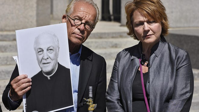 Attorney Jeffrey Anderson holds a photograph of deceased priest Donald Rieder while standing with Susan Fuchs-Hoeschen during a press conference Tuesday on the steps of the Stearns County Courthouse.