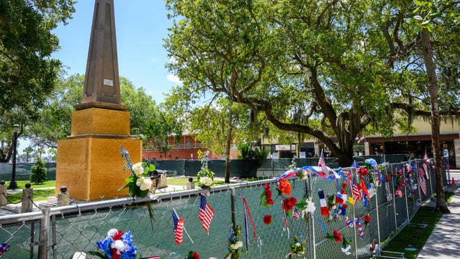 Flags, flowers and messages decorate the temporary fence surrounding the Confederate memorial on the Plaza de la Constitucion in St. Augustine on June 29.