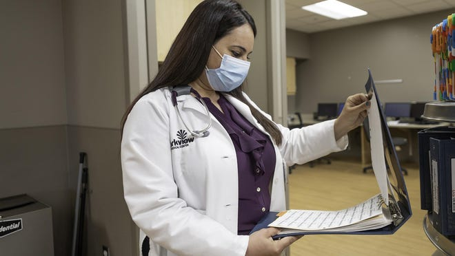 Dr. Widian Jubair looks through patient records at Parkview Medical Center on Tuesday. A native of Iraq, Jubair is in the final year of a three-year residency.
