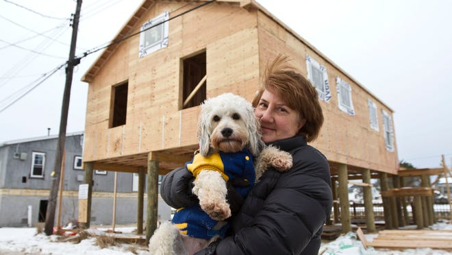Kathy Gerndt of Bridgewater, seen here with her dog Sassy, has rebuilt her family's home in the Ocean Beach 3 section of Toms River. JCP&L has told her the house is now to close to the utility pole, so she must pay for a new pole.
