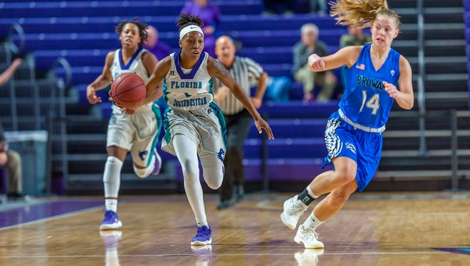 Florida SouthWestern State guard Erna Normil (center) signed with Florida Gulf Coast University on Wednesday, April 25, 2018.