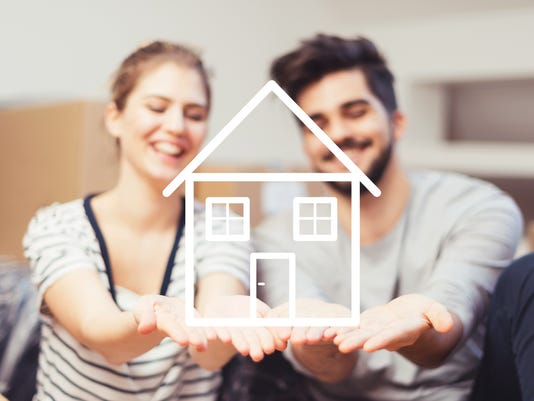 Young couple holding their new, dream home in hands
