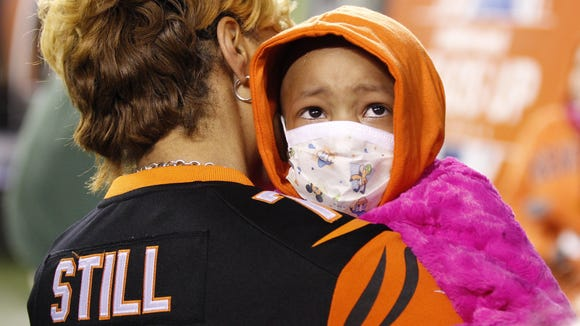 Leah Still gets a hug on the Paul Brown Stadium field as Bengals fans call her name. Nearly $1,350,000 was donated to cancer in Leah's honor.