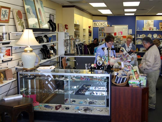 Kathy Kulper helps a customer check out at the Discovery Shop, Oct.17, 2017